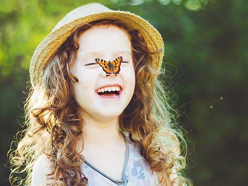 Smiling little girl with butterfly on nose