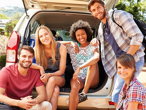 Smiling group of friends sitting in open car boot