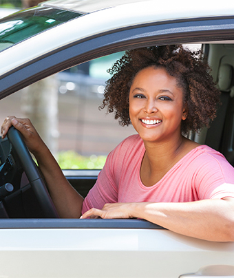 Smiling woman inside a car holding the steering wheel