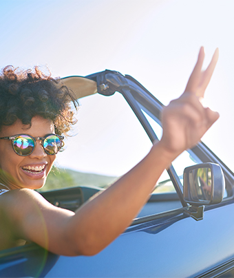 Smiling woman inside a drop top convertible holding up a peace sign