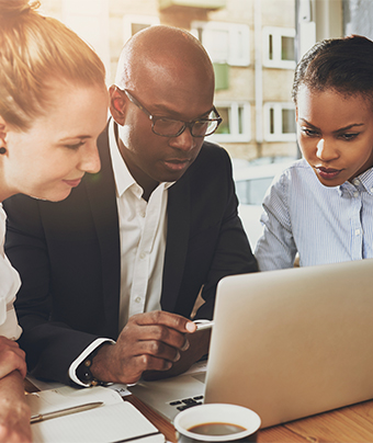 Man and 2 women looking at a laptop screen