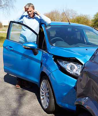 Blue car crushed behind a grey car with stressed man on the phone standing at the blue car driver's door