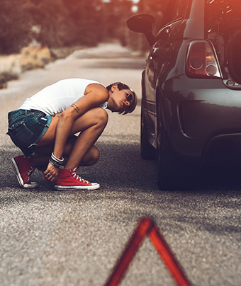 Woman squatting and looking at a car wheel