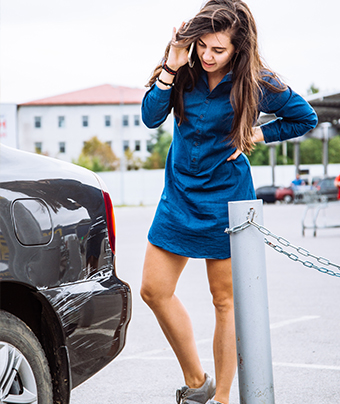 Woman in a blue dress on the phone looking at a dent on the left back side of a car