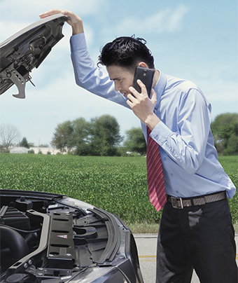 Man on the phone while holding open the bonnet cover of a car with vegetation in the background