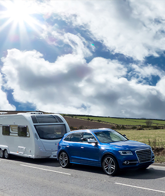 Blue car towing a white caravan with cloudy sky in the background