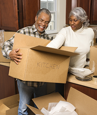 Woman unpacks box while smiling man holds it up for her
