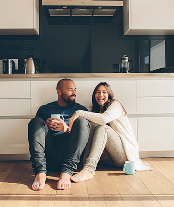 Man and woman sitting on the floor smiling.