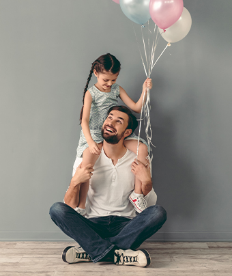 Little girl holding balloons while sitting on man's shoulders