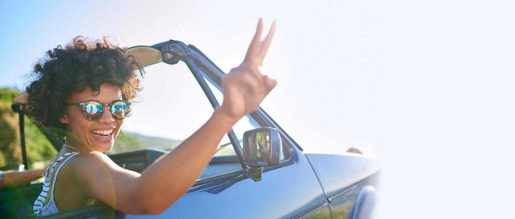 Woman in a car wearing shades with 2 fingers up