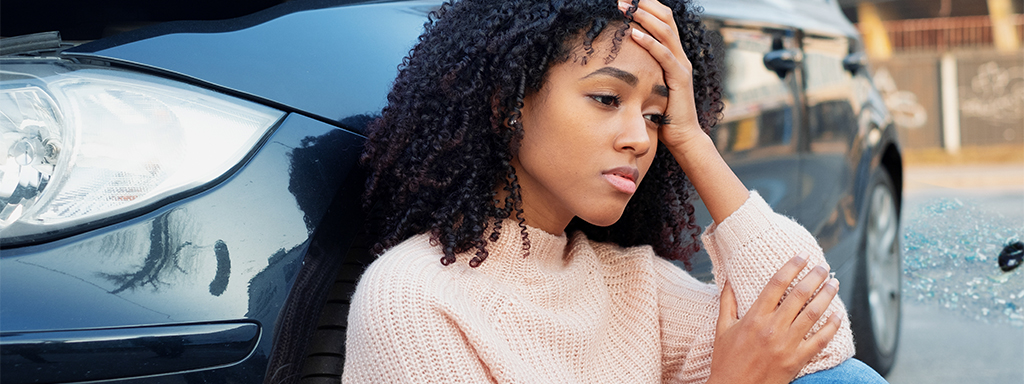 Woman sitting next to a car holding her forehead
